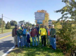 Frederick Pedalers pose in front of the sign on Bethel Road after a successful trash pickup.